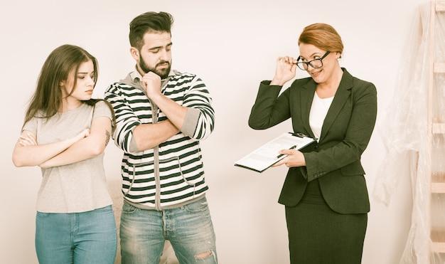 不動産業者は、オープンハウスで若いカップルに無愛想な同意を示します