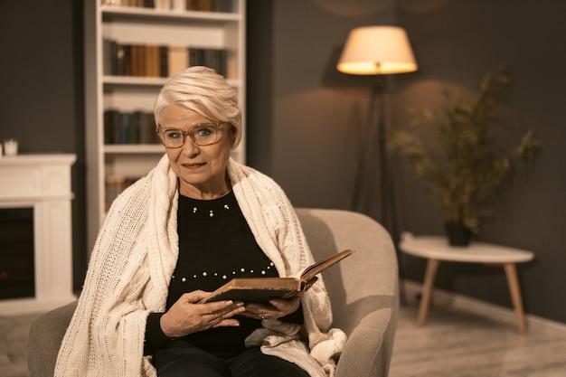 彼の手で古い本を保持している肘掛け椅子で休んでいる高齢者の女性