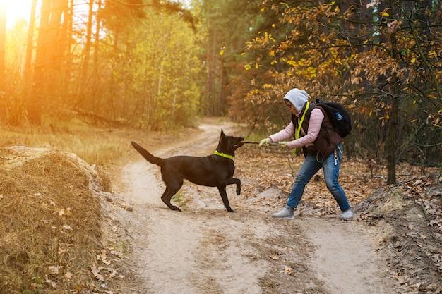 女性が森でハイキングしながら彼女の犬を訓練