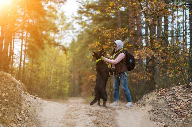 屋外の森で彼女の犬を訓練する女性