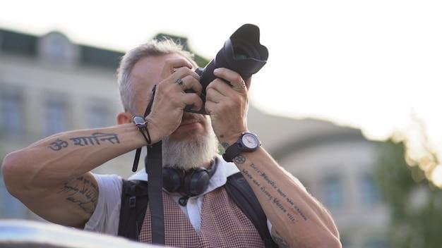 カメラを持つヨーロッパの男性は、夏の夜にトリガーを引っ張る