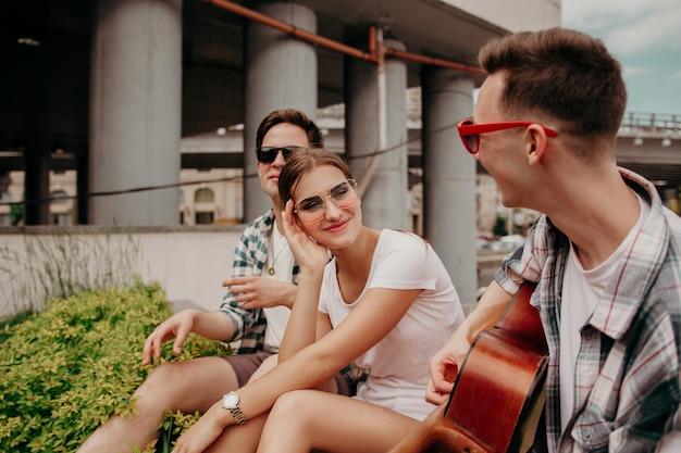 ギターを弾くティーンエイジャーの学生