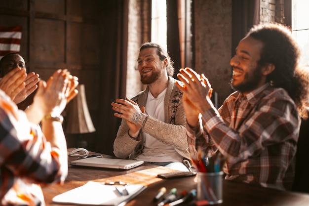 Разнообразная команда партнеров приветствует друг друга в офисе
