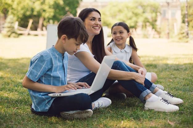 Учитель и двое молодых студентов используют ноутбук в парке