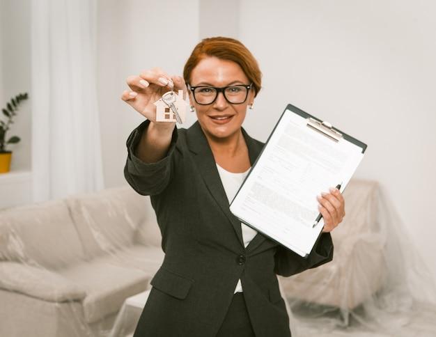 全米リアルター協会加入者がアパートの家賃の契約に署名することを提案し、カメラは手で鍵を保管することに焦点を合わせました。