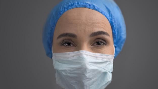 Женский медик в защитной маске и синей кепке, крупным планом лицо, изолированное на серой спине