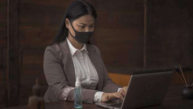 Азиатская женщина в маске работает на ноутбуке в офисе