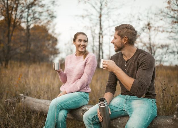 Влюбленная пара пьет горячий напиток на природе