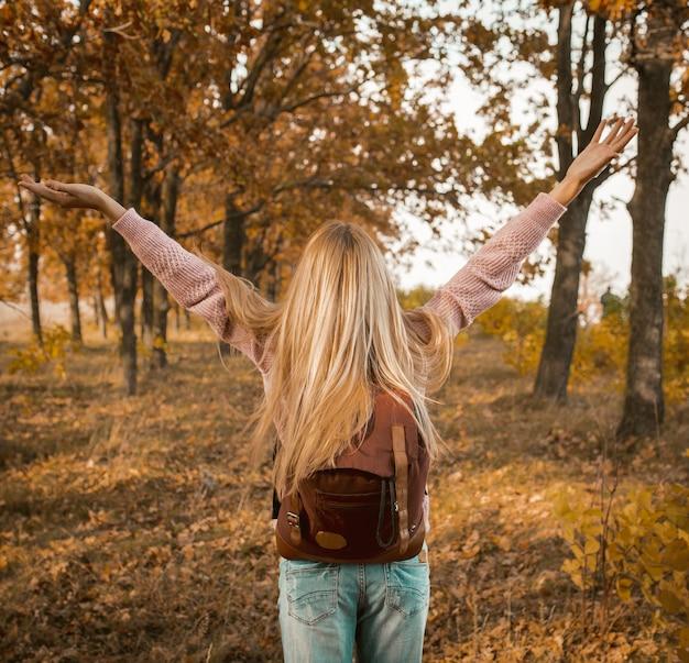 Вид сзади счастливой блондинки с поднятыми руками в осеннем лесу