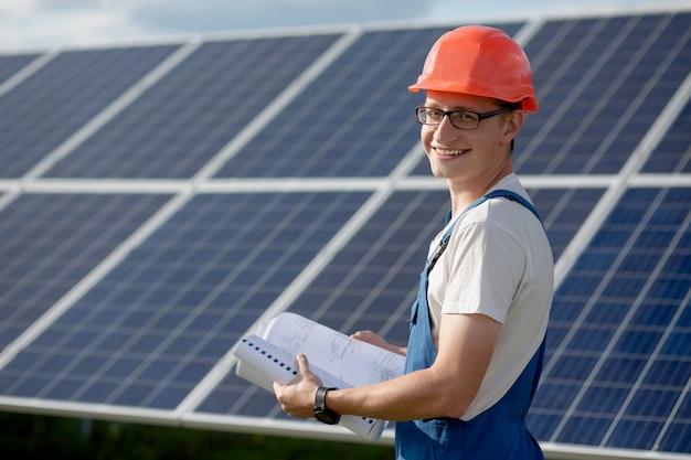 若い男が太陽電池パネルを操作します。