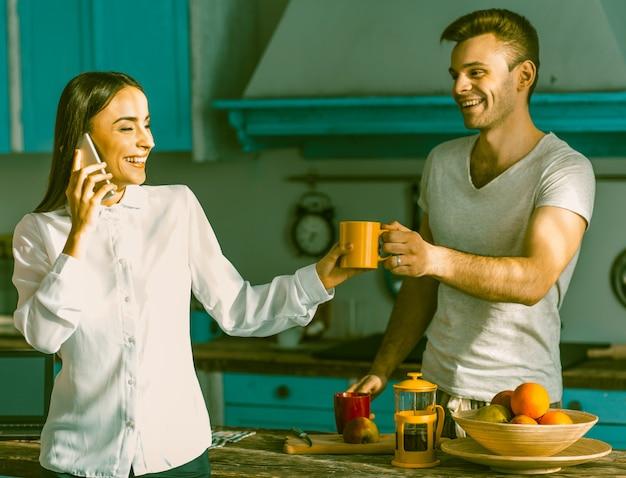 晴れた朝にキッチンでチャット幸せなカップル