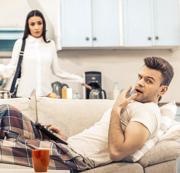 パジャマ姿の男がソファに横たわっている間あくび