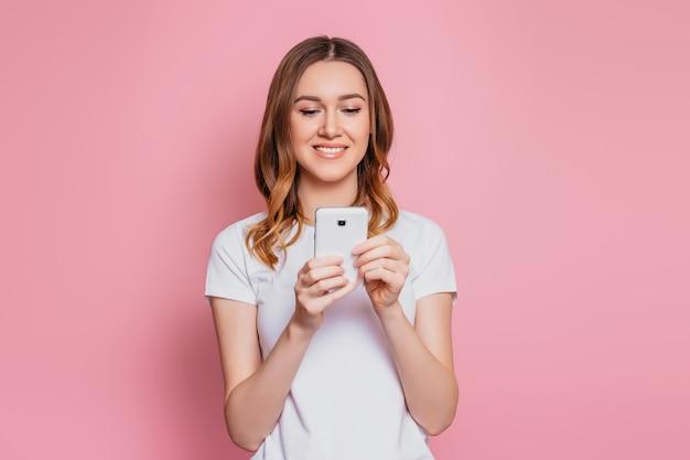 Портрет счастливой молодой женщины кавказа в белой футболке с помощью мобильного телефона, изолированных на розовой стене девушка студентка с волнистыми вьющимися волосами смотрит на смартфон и читает сообщение