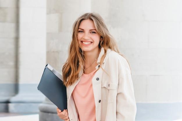 大学に対して笑みを浮かべて若いブロンドの女の子の学生。かわいい女子学生は手でフォルダーとノートブックを保持しています。学習、教育のコンセプト