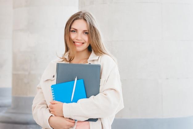 大学に対して笑みを浮かべて若いブロンドの女の子の学生。かわいい女子学生がフォルダーとノートを手に保持している、コピースペース。学習、教育のコンセプト