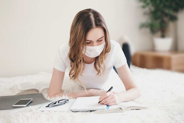 医療用防護マスクを身に着けている学生の女の子は、本、ノートブックが付いているベッドに横たわっています。若い女性が自宅でノート、遠隔教育、家庭教育、コロノウイルス、検疫に書き込みます