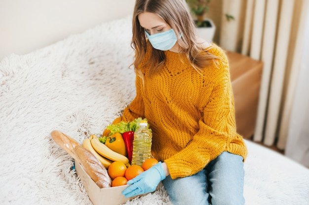 Молодая девушка-волонтер в медицинской маске держит картонную коробку с веганской едой, фруктами и овощами и садится на диван, доставка на дом, короновирус, карантин, концепция пребывания дома