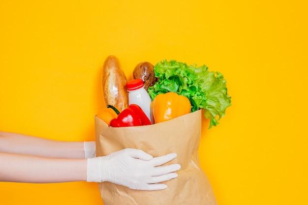 医療用手袋の女性の手は、食品、野菜、コショウ、バゲット、ヨーグルト、黄色の壁で隔離された新鮮なハーブ、検疫、コロナウイルス、安全なエコフードショッピングの配達で紙袋を保持しています。