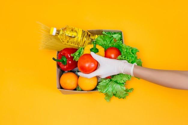Женские руки в медицинских перчатках держат помидор над картонной коробкой с едой, маслом, перцем, перцем чили, апельсинами, помидорами, макаронами, изолированными над оранжевым пространством