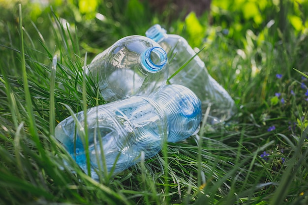 Пластиковые бутылки в траве, загрязнение окружающей среды, экологические проблемы, разрушение экосистемы с помощью пластика. мусор, отходы