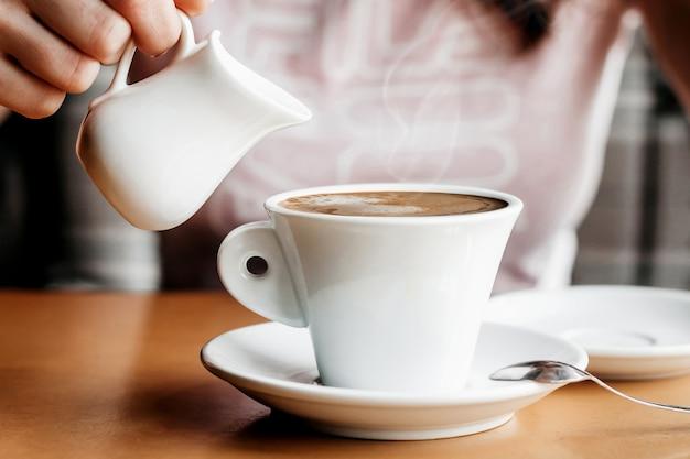 モーニング・コーヒー。カフェでコーヒーカップを持つ女性の手のクローズアップ。女性両手カフェ、ヴィンテージ色のトーンで木製のテーブルの上にコーヒーのカップ