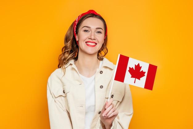 Девушка студент улыбается и держит маленький флаг канады, изолированных на оранжевом фоне