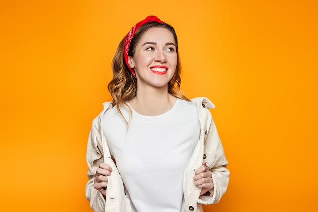Девушка в белой футболке, улыбаясь, изолированных на оранжевом фоне