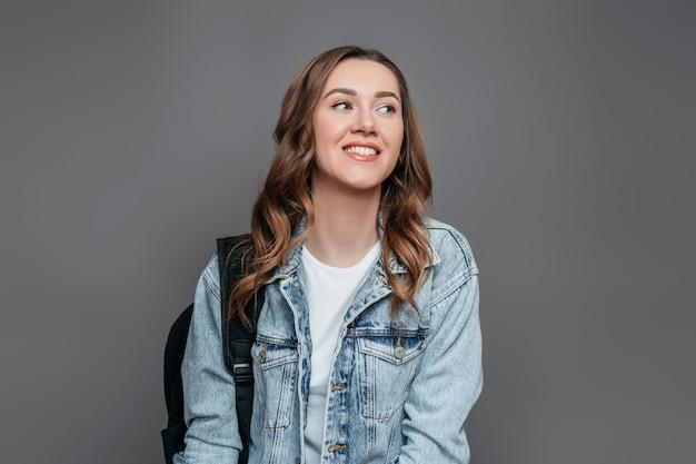Портрет молодой улыбающейся девушки в белой футболке и джинсовой куртке на темно-сером фоне