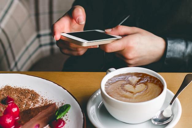 携帯電話、コーヒー、カフェでケーキを持つ少女。