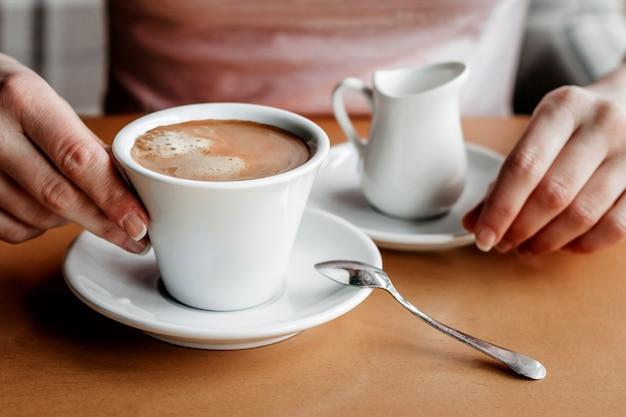 モーニング・コーヒー。カフェでコーヒーカップを持つ女性の手のクローズアップ。