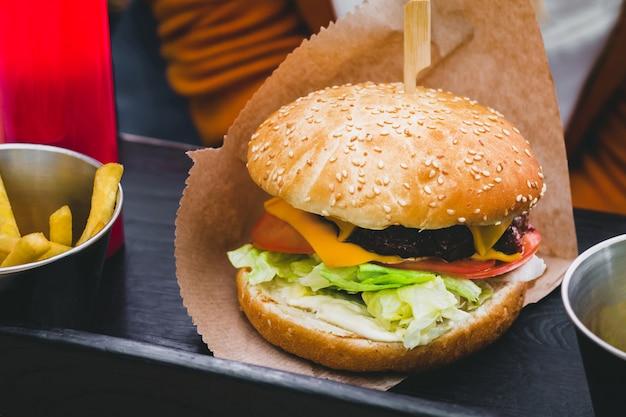 黒い木製のテーブルにフライドポテトと新鮮なおいしいハンバーガー