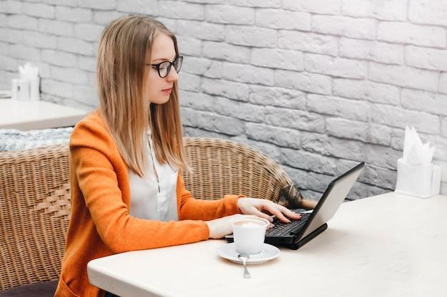 ノートパソコンと一杯のコーヒーとカフェでブロンドの女の子。若い女の子のフリーランサーのラップトップに取り組んで