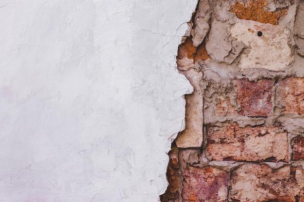 グランジのヴィンテージのレンガの壁の質感と白い漆喰の建物のファサードの背景