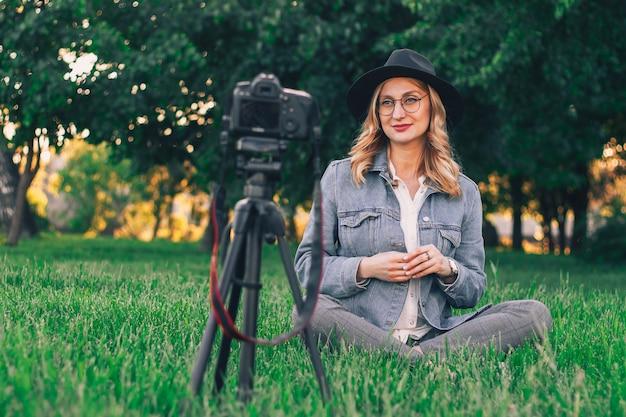 Стильная девушка-блогер сидит в парке и снимает влог на камеру.