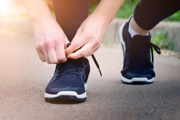 朝が走っています。実行する前に靴ひもを結ぶ少女
