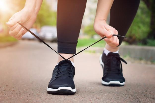 朝が走っています。黒いスニーカーで日没時に田舎道を走っている若い女性