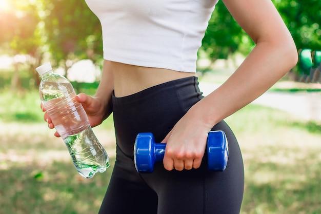 Девушка держит гантель и бутылку минеральной воды