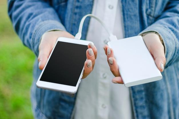 Банк силы удерживания девушки и умный телефон. девушка заряжает свой смартфон, используя зарядное устройство.