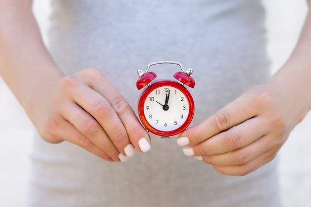 妊娠中の女性は彼女の手に赤い目覚まし時計で白いレンガの壁に立っています。妊娠、目覚まし時計と誕生時間の概念をクローズアップ