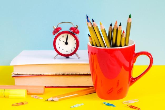 青色の背景に赤い目覚まし時計、色鉛筆、書籍、カエデの葉。
