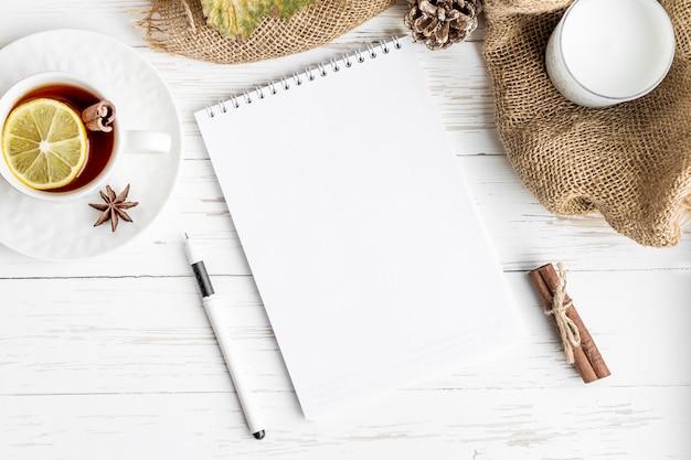 ノートブック、熱いお茶、ペン、白い木製のテーブルの上のろうそく。モックアップ