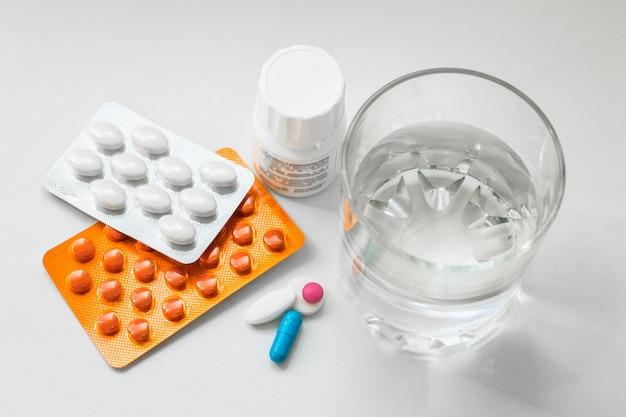 ブリスター、カプセル、白い背景の上の水のガラスの丸薬。風邪、ビタミン、健康複合体の治療のための準備