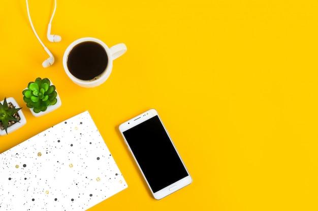 朝のコーヒー、ノート、携帯電話、黄色の植物