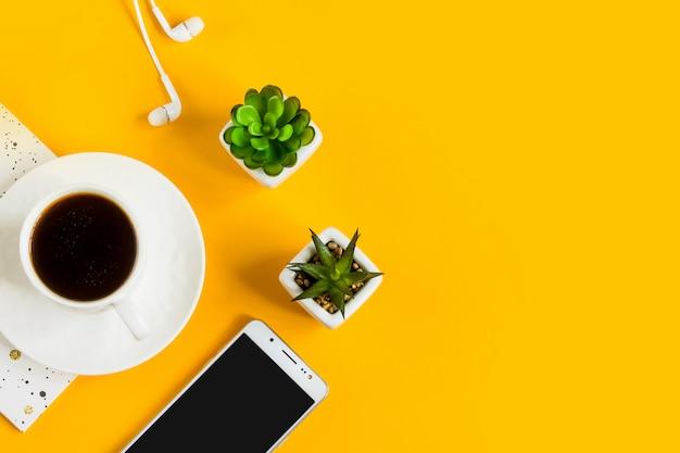 朝のコーヒー、ノート、携帯電話、黄色の背景の植物。ビジネス黄色の背景。
