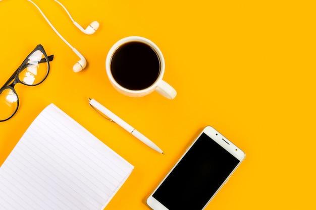 ノートブック、スマートフォン、モバイル、コーヒー、ペン、メガネ、黄色の背景に。コピースペース。上面図。平干し