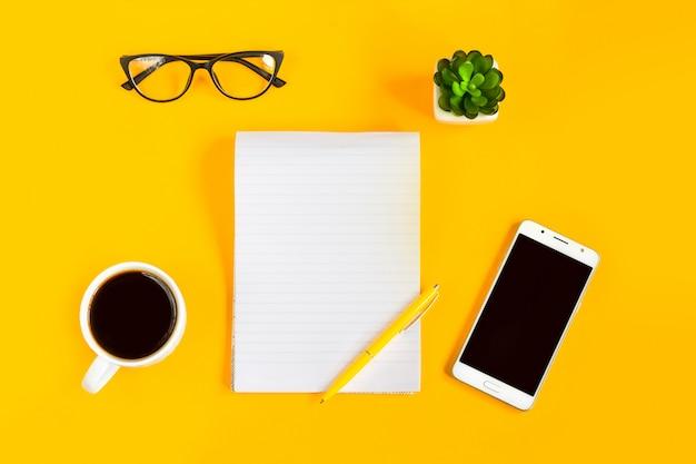 ノートブック、携帯電話、モバイル、コーヒー、ペン、黄色の背景にメガネ。コピースペース。上面図。