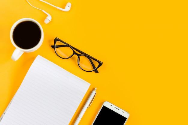 ノートブック、携帯電話、モバイル、コーヒー、ペン、黄色の背景にメガネ。コピースペース。上面図。平干し