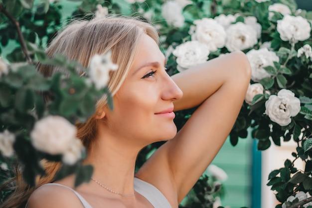 白いバラの茂みの髪型と美しいブロンドの女の子の肖像画。ウェディングフォトセッション