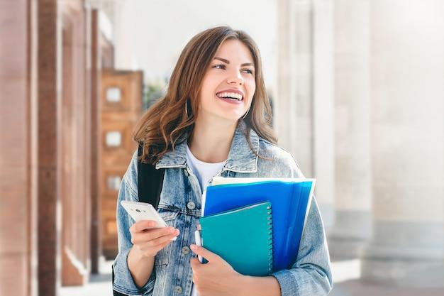 若い女子学生が大学に対して笑顔します。かわいい女子学生は、フォルダー、ノートブック、携帯電話を手に保持しています。学習、教育