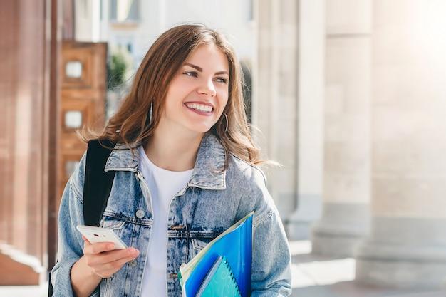 Студент маленькой девочки усмехаясь против университета. милая девушка студент держит в руках папки, ноутбуки и мобильный телефон. обучение, воспитание